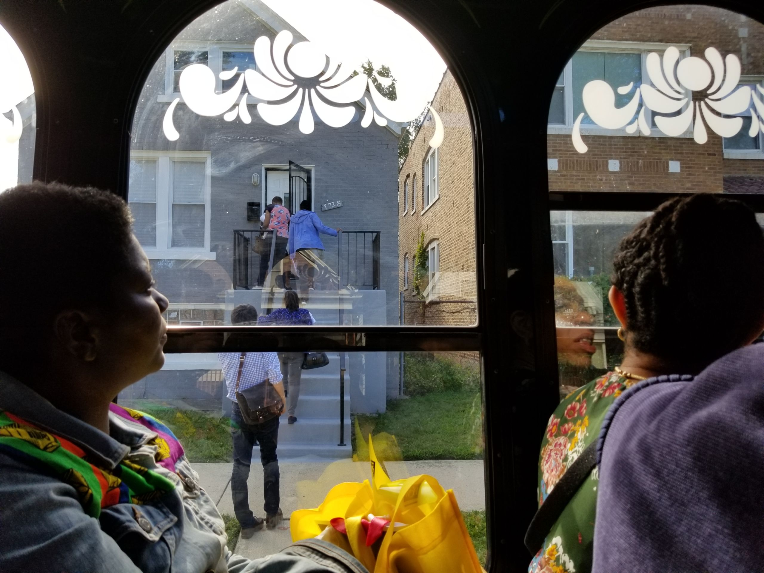 Through a the window of a trolley, the image shows people filing into a home in Chatham to look inside. Inside the trolley, others look at the house out of teh window.