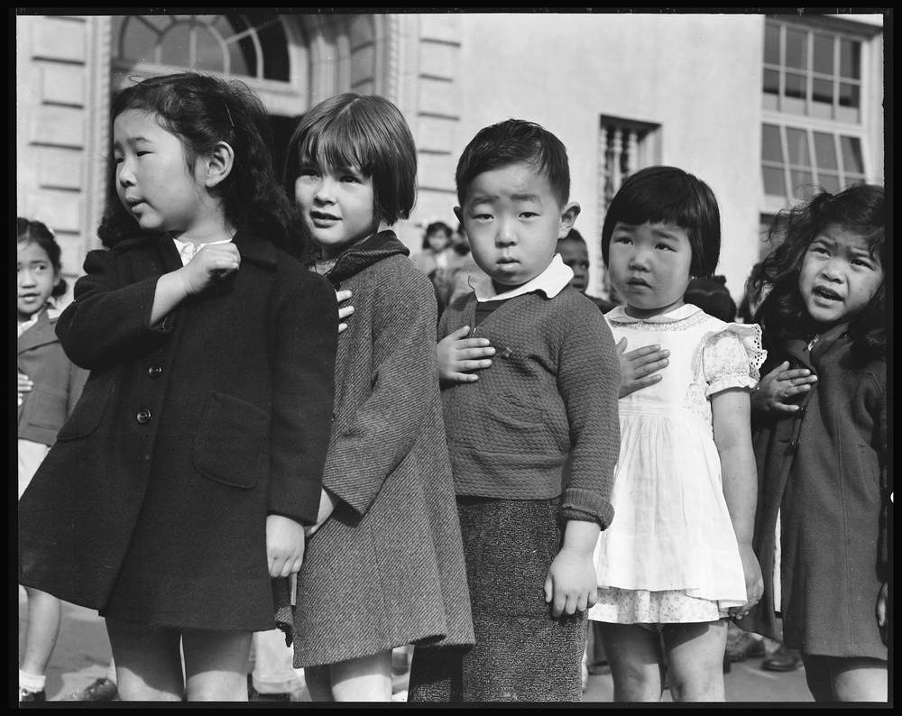 In April 1942 — days before they were forcefully relocated — Japanese-American students in San Francisco began their morning by reciting the Pledge of Allegiance. (Dorothea Lange, War Relocation Authority)