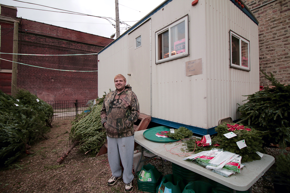 "Chris Peterson, 34, of Wisconsin, mans the Arneson Christmas tree lot in Chicago's Old Town neighborhood. He lives in the on-site trailer. ""We've got our cold days, but we have heat in there,"" he says, adding that he's grateful for the job. ""It helps out quite a bit at the end of the year. ... It helps out with presents and the family."" (WBEZ/Katherine Nagasawa)"